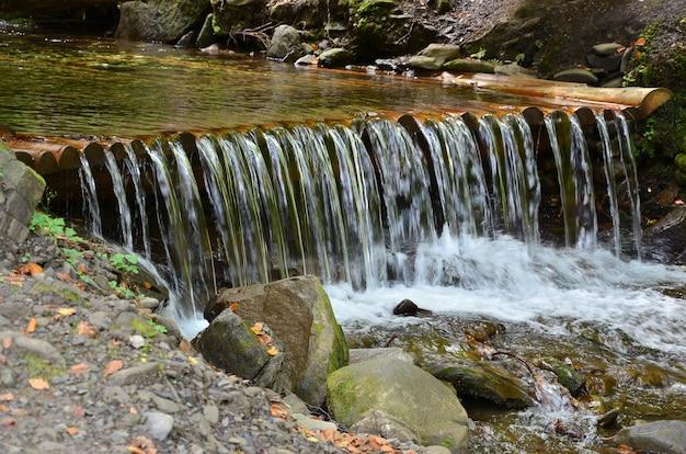 L'eau en bois faite à la main s'écoule de petites poutres traitées