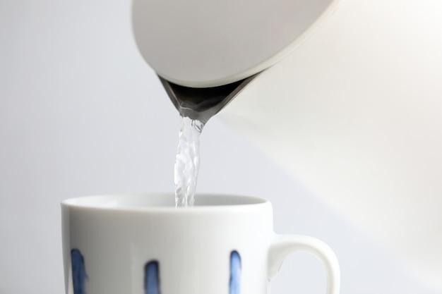 Eau bouillante ruisselant dans une tasse blanche de la bouilloire