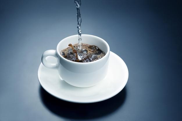 L'eau bouillie de la bouilloire est versée dans une tasse blanche pour le café