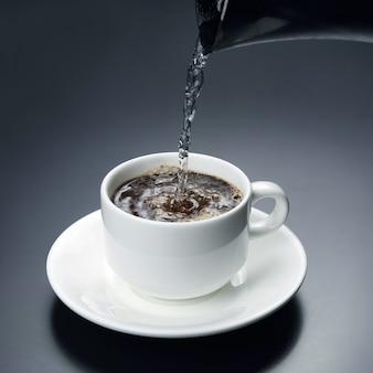 L'eau bouillie est versée dans une tasse blanche avec du café noir. boisson chaude