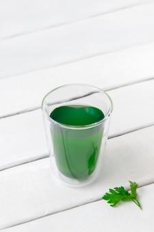 Eau avec de la chlorophylle liquide dans un verre sur une table en bois blanc avec copie espace image verticale