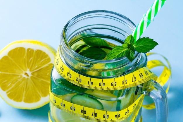Eau citronnée, citron juteux, un morceau de menthe fraîche et un ruban à mesurer
