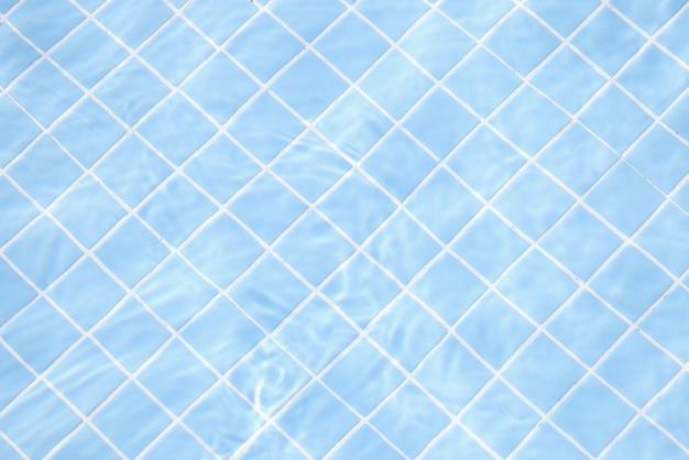Eau claire transparente dans la piscine sur fond de carreaux bleus