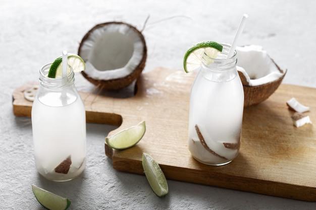 L'eau de coco en bouteilles sur fond clair. boisson végétarienne saine
