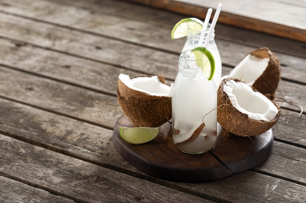 L'eau de coco en bouteilles sur une table en bois. boisson végétarienne saine