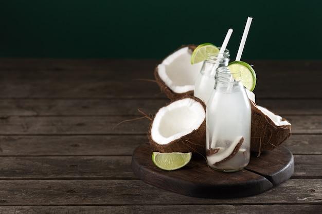 L'eau de coco en bouteilles sur table en bois. boisson végétarienne saine