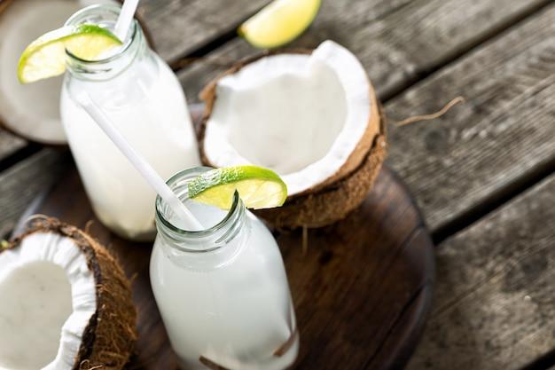 L'eau de coco en bouteilles sur une table en bois. concept de boissons saines