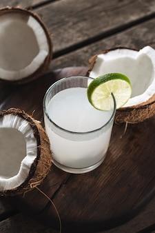 L'eau de coco en bouteilles sur table en bois. concept de boissons saines