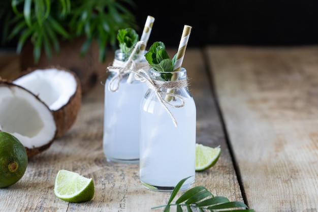 L'eau de coco fraîche dans une bouteille en verre sur la table. boisson végétarienne. espace copie