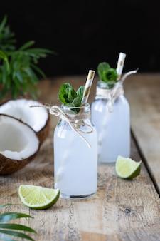 L'eau de coco fraîche dans une bouteille en verre sur la table. boisson végétarienne.