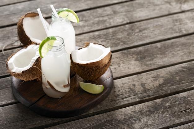 L'eau de coco fraîche dans des bouteilles sur une table en bois