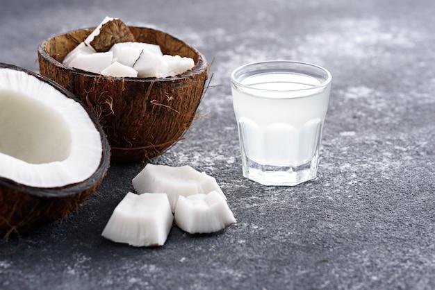 Eau de coco à la mode en verre, moitiés de noix de coco sur fond gris