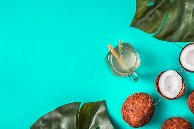 L'eau de coco et les noix de coco sur un avec des feuilles tropicales.