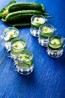 Eau de concombre dans six petits bocaux en verre sur surface bleue