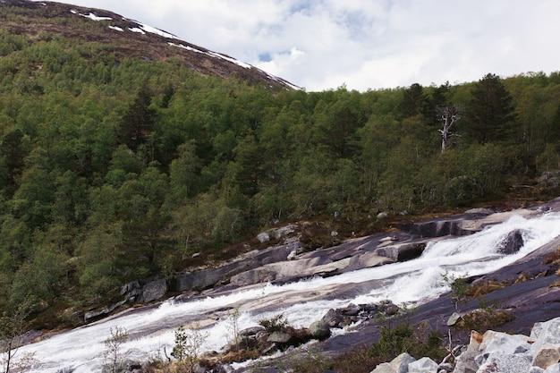 L'eau coule sur les rochers dans les montagnes