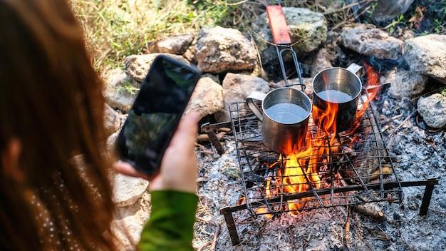 L'eau dans deux tasses en étain bout sur un feu de camp