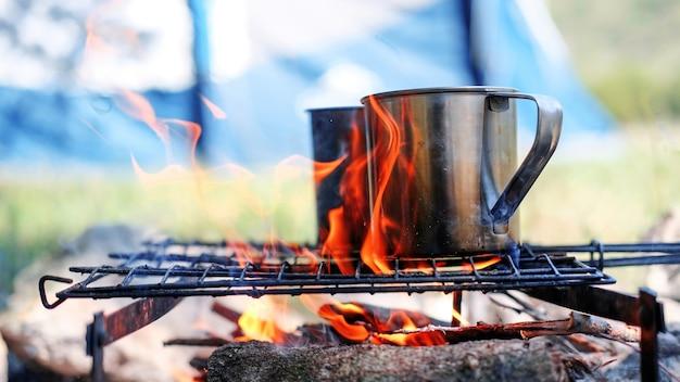 L'eau dans deux tasses en étain bout sur une grille au-dessus du feu de camp