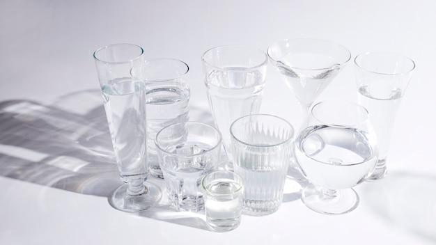 Eau dans différents types de verres avec une ombre sur fond blanc
