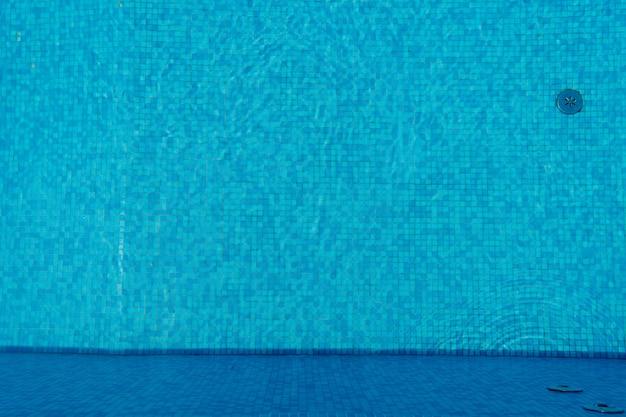 Eau dans la piscine, fond avec tuiles bleues. section baignade et vacances à la plage. installations de purification de l'eau dans la piscine.