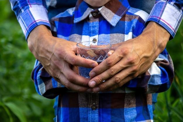 De l'eau dans un verre entre les mains d'un enfant et d'un père. la nature.