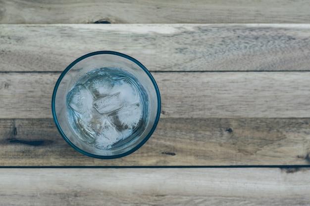 L'eau dans un verre avec de la glace mer pose un plancher en bois. focus sur la glace derrière le flou