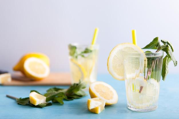 Eau de désintoxication fraîche faite maison avec des citrons sur fond gris et assis sur un bureau vintage bleu