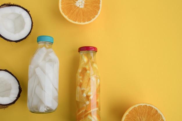 Eau de désintoxication à la noix de coco et à l'orange dans les bouteilles en verre sur fond jaune. vue de dessus. espace de copie.