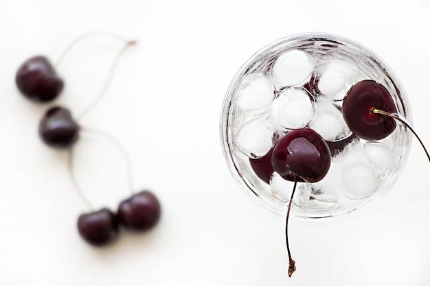 Eau de désintoxication rafraîchissante avec cerise et glaçons dans un verre.
