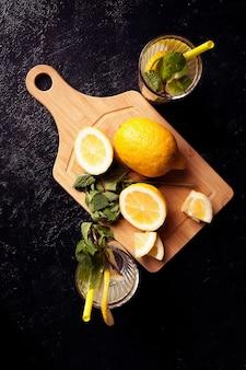 Eau de désintoxication saine et délicieuse avec des citrons sur fond de bois vintage