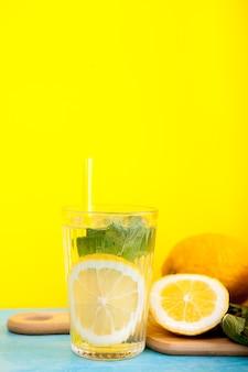 Eau de désintoxication savoureuse et biologique avec des citrons sur fond jaune en photo de studio