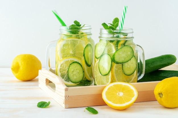 L'eau de désintoxication avec des tranches de citron et de concombre dans un pot sur une table en bois.
