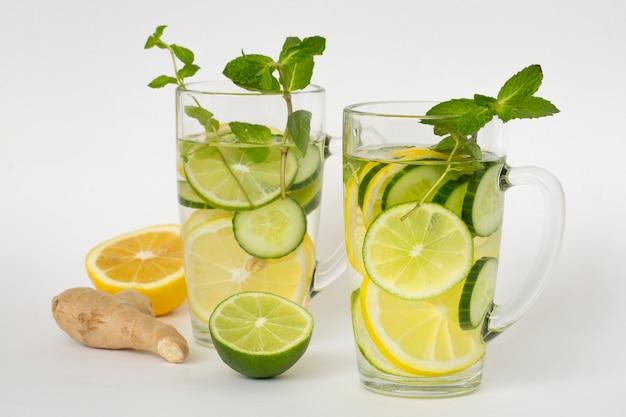 Eau détox au citron lime concombre gingembre et menthe et ingrédients pour sa préparation. aliments sains riches en vitamines et antioxydants