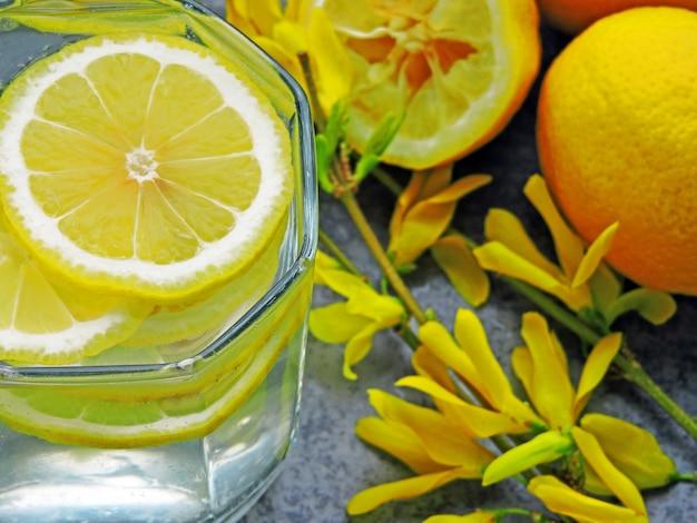 Eau détox avec jus de citron et fleurs jaunes sur les branches.
