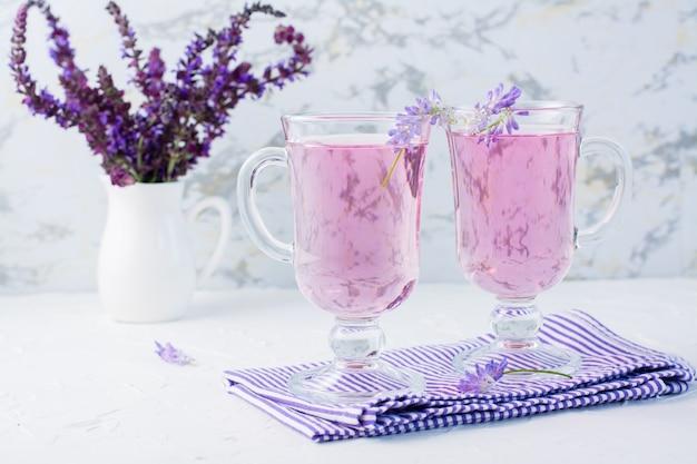 Eau douce avec de la lavande dans des verres et un bouquet de fleurs dans une cruche sur la table. cocktail aromatique à la lavande