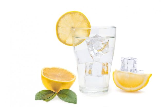 De l'eau, du citron et des glaçons dans un verre. tranches de citron et de lin à côté d'un verre. isolé.
