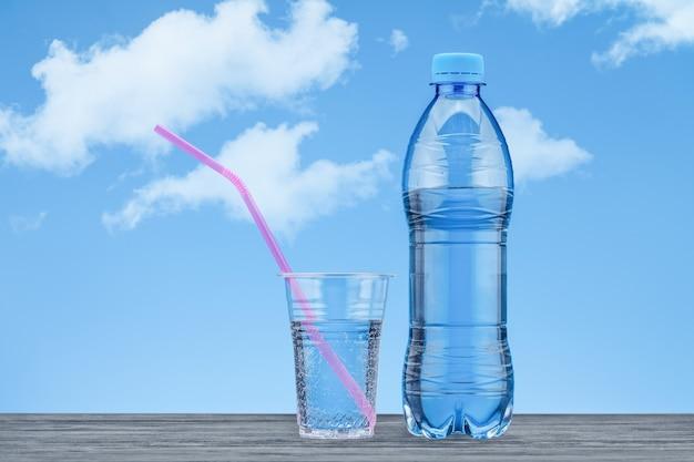 L'eau avec du gaz est en verre avec de la paille rose et une bouteille en plastique avec de l'eau contre le ciel bleu avec des nuages.