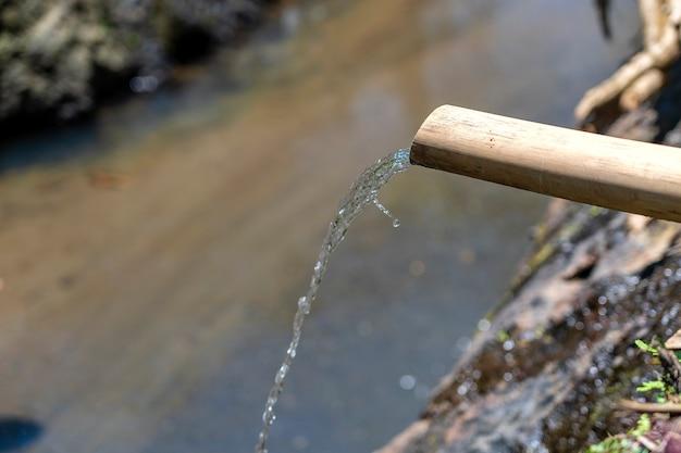 L'eau du tube de bambou se jette dans la rivière à ubud, île de bali, indonésie. fermer