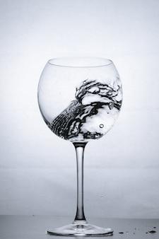 Eau éclaboussant dans le verre à vin de luxe se bouchent