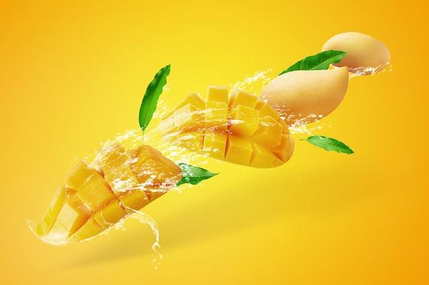 Eau éclaboussant sur les fruits frais mangue en tranches avec des cubes de mangue isolé sur jaune