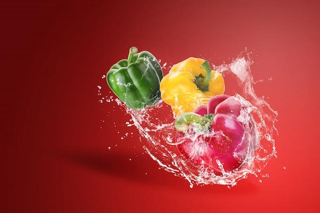 De l'eau éclaboussant des poivrons rouges, jaunes et verts tirés sur un fond rouge.