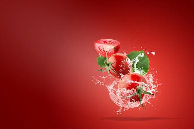 Eau éclaboussant sur les tomates rouges fraîches sur rouge