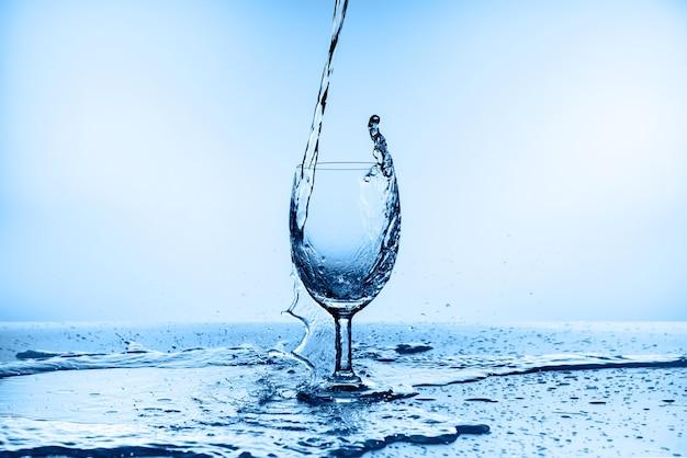 De l'eau éclaboussant de verre isolé sur bleu