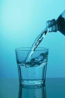 L'eau est versée dans un verre sur un mur bleu, close-up