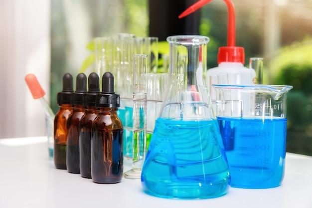 Eau expérimentale bleue dans un bécher et une fiole dans un laboratoire de sciences chimiques. groupe de flacons de laboratoire avec liquide à l'intérieur. les chercheurs développent des vaccins et des médicaments pour traiter le virus covid-19.