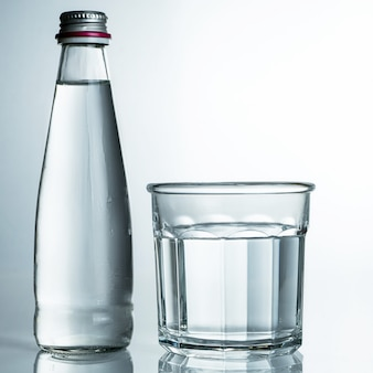 Eau fraîche et froide pure dans un verre avec bouteille. l'eau purifiée dans un verre sur une table grise. eau sur table grise.
