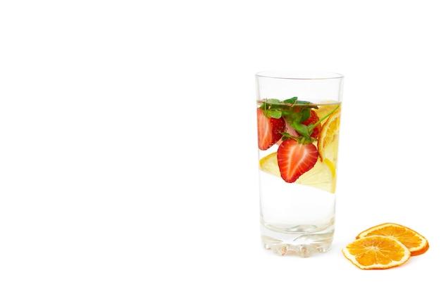 Eau avec des fraises et du citron dans un verre transparent