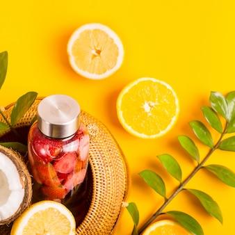 Eau avec des fraises, des oranges, des citrons et des noix de coco sur jaune avec un sac de paille