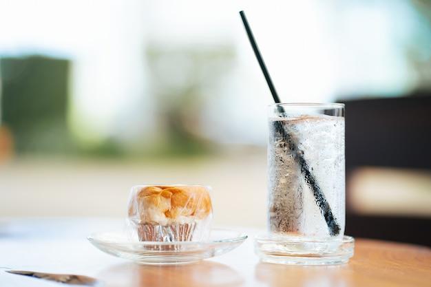 Eau froide dans un verre et pain de petit-déjeuner. mise au point sélective.