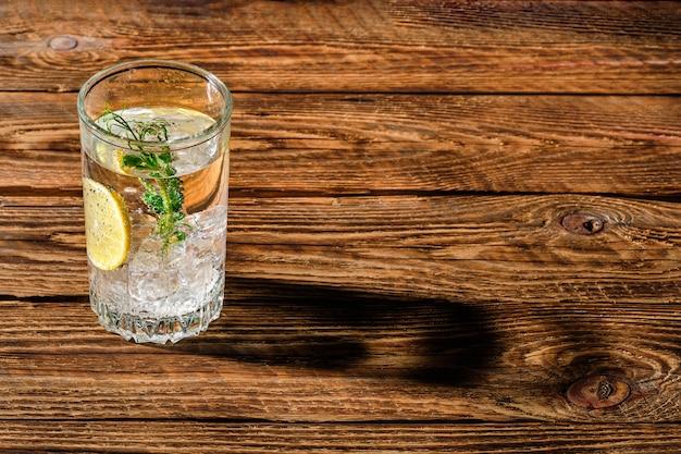 Eau froide gazéifiée avec de la glace et du citron laissant tomber une longue ombre sur une table en bois