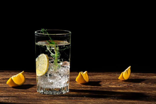 Eau froide gazéifiée avec de la glace et du citron projetant une ombre sur une table en bois